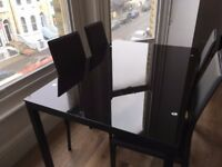 Almost unused modern black glass dining table with 4 chairs