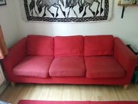 Red preloved three seater sofa.