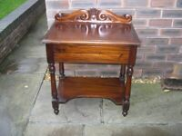A polished mahogany hall table with drawer and carved back.