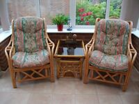 Pair of cane conservatory chairs with coffee table.