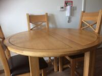 Oak circular dining table and four chairs
