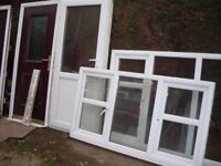 nice back door with flag hingers and key and 2 living room and kitchen windows
