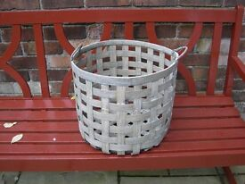A two handled cane/ bamboo log basket.