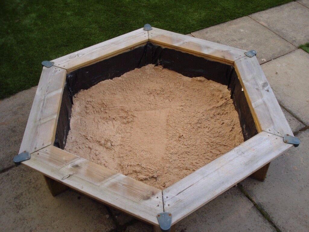 Wooden framed kids sit in sandpit