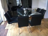 Beautiful glass dining table and eight leather chairs
