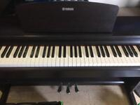 Yamaha electronic piano with Pedals and headphone sockets.