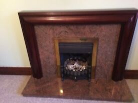 Dark wood fire surround with marble hearth and back panel