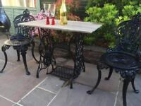 Cast iron table with new chairs .