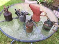 Old oil cans and a brass blow lamp.