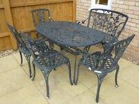 Cast Iron garden set : table, 4 chairs , bench , pretty rose design .