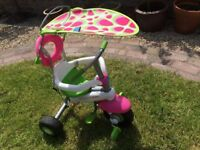 A LITTLE GIRLS PINK AND GREEN SMART TRIKE