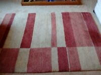 """Wool. RUG 72"""" x 50"""" Shades of red, cream and wheat."""