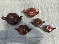five brown teapots of various sizes