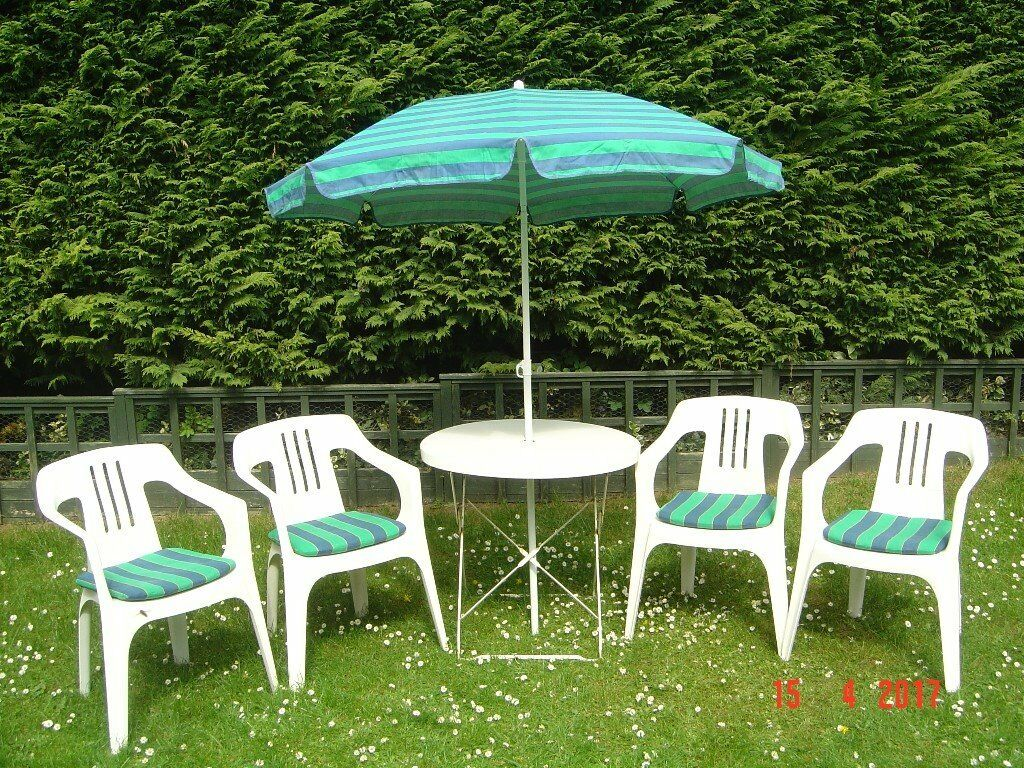 white metal circular patio table with four plastic chairs plus cushions and a parasol can - Garden Furniture Yate