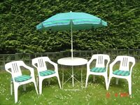 White Metal Circular Patio Table with Four Plastic Chairs plus Cushions and a Parasol. Can Deliver.