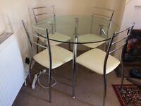 Circular glass top dining table and four chairs.