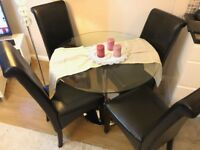 Glass Dining Table with black upholstered chairs