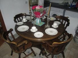 Colonial circular dark wood table and four captain chairs.