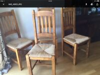 Qty 4 solid wood oak dining chairs with rush seats.
