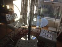 Circular glass and chrome dining table