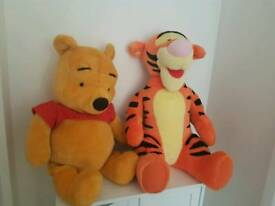Large winnie the pooh and tigger cuddly toys.