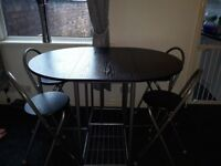 Black fold away dining table with 4 stool chairs
