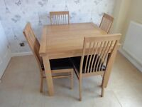 Oak dining table and four leather chairs.