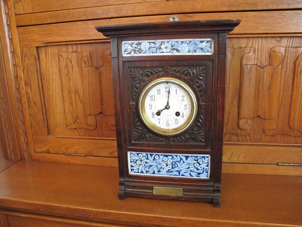 Carved oak clock by J W Benson with tile decoration