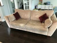 Brown three seater sofa with red cushions.
