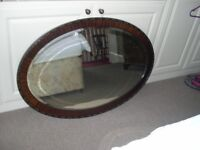 An attractive large wood framed oval mirror with bevelled edges.