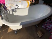 Free standing cast iron slipper bath with telephone style taps.
