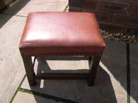 A wood framed brown leather seat stool.