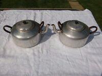 a pair of vintage aluminium teapots