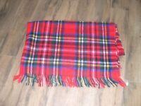 A tartan travel rug with fringe.