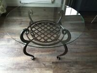 Stylish glass topped dining table on wrought iron base