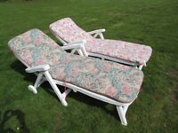 Pair of white plastic reclining garden sun lounger chairs with cushions / pads