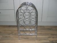 A chrome plate metal wine rack with 14 bottle capacity.