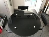 Glass round dining table and four chairs
