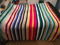 A crotcheted blanket I made. Can be used for a bed or a sofa. Colourful and stripey.