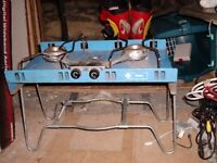 Two burner camping cooker. Stands over smaller calor gas bottle. Ideal, not too heavy . Easy set up