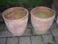 Two identical attractive round terracotta planters.