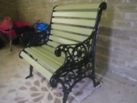 SOLID WOOD SLATTED AND WROUGHT ENDS GARDEN SEAT. COMPLETELY RE-FURBISHED. STUNNING GARDEN CHAIR.