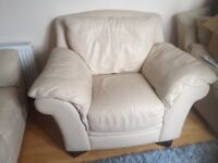 Two cream leather large comfortable armchairs.