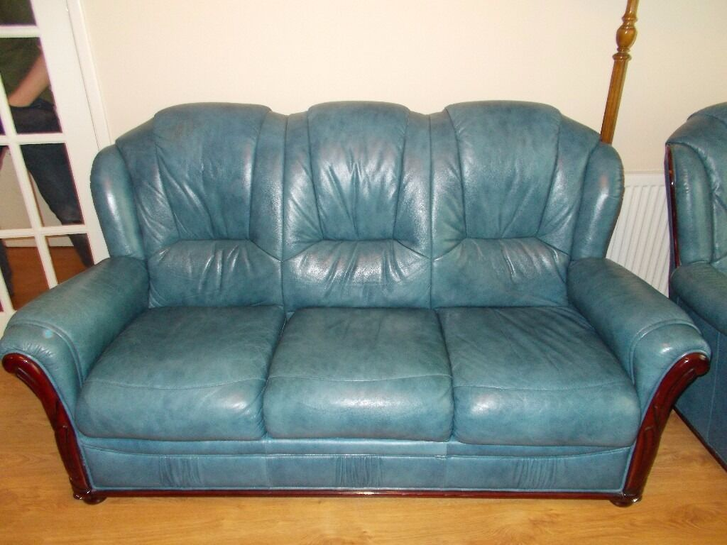 Blue leather four piece suite. 2 arm chairs, one three seater sofa and footstool. v.good condition