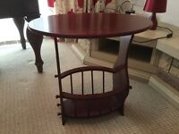 Dark wooden oval shaped coffee table with book magazine stand on the bottom
