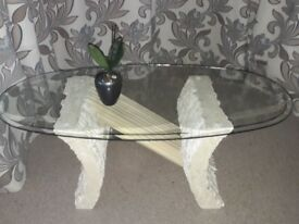 Oval bevelled glass coffee table with stone effect base.
