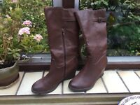 Mid calf length brown boots size 6. These boots have a wedge heel and a side zip.