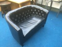 Two seater black button back faux leather sofa
