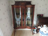 Double bowed glass cabinet.