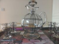 Beautiful glass decanter with stopper with four matching glassesses with black and silver pattern